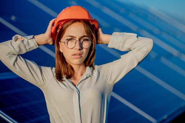 Mooie jonge ingenieur permanent in de buurt van zonnepanelen buitenshuis