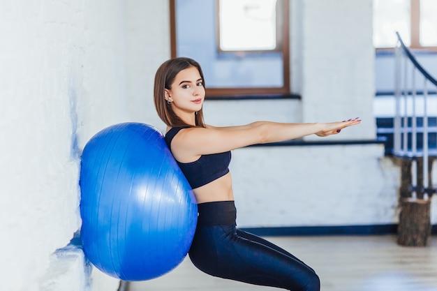 Mooie jonge instructeur steekt de armen uit en doet oefeningen met blauwe bal