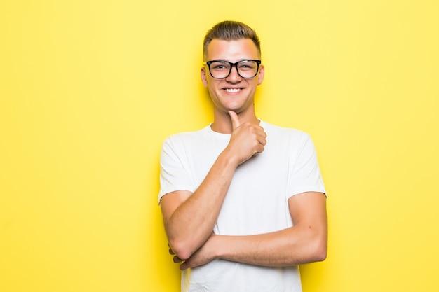 Mooie jonge jongen houdt zijn hand onder zijn kin, gekleed in een wit t-shirt en een transparante bril