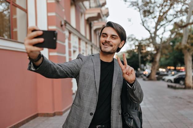 Mooie jonge jongen met donkerbruin haar en borstelharen, staande in zwart t-shirt en grijze blazer, videochatten op telefoon en glimlachen, tegen stadsstraat