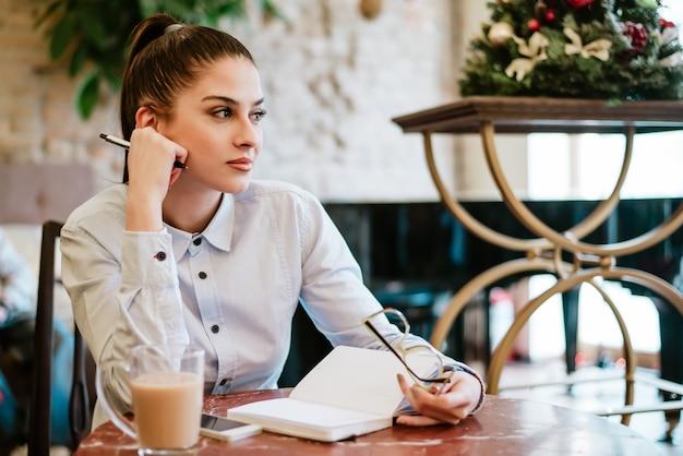 Mooie jonge journalist werkpauze genieten van koffie.