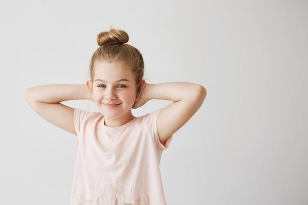 Mooie jonge juffrouw met blauwe ogen en licht haar in roze t-shirt poseren met schattige knot kapsel en handen achter het hoofd voor familiefoto.