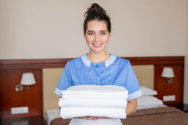 Mooie jonge kamermeisje met stapel witte schone handdoeken terwijl ze haar werk in de hotelkamer doet