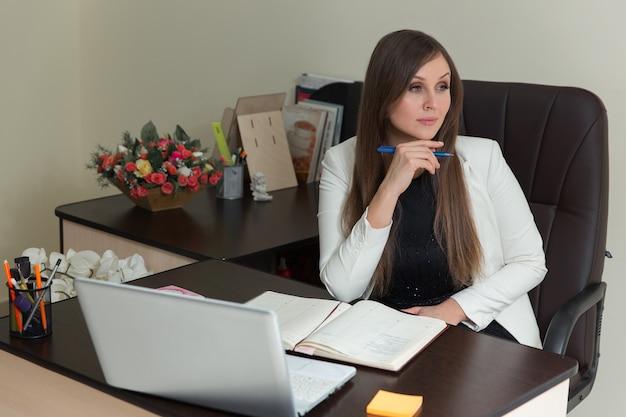 Mooie jonge kantoorvrouw zit aan haar bureau met notities en laptop, met een peinzende gezichtsuitdrukking terwijl ze omhoog kijkt.