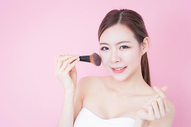 Mooie jonge kaukasische aziatische vrouwenglimlach die de kosmetische natuurlijke make-up van het borstelpoeder toepast