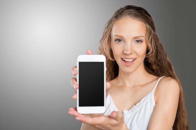 Mooie jonge kaukasische bedrijfsvrouw met slimme telefoon
