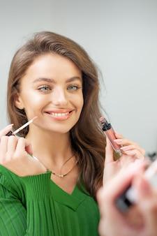 Mooie jonge kaukasische glimlachende vrouw die glans toepast op de lippen die in de spiegel kijken