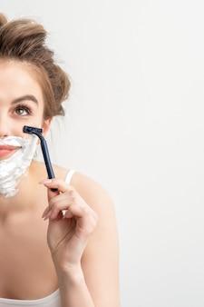 Mooie jonge kaukasische glimlachende vrouw die haar gezicht met scheermes scheert dat op witte achtergrond kijkt