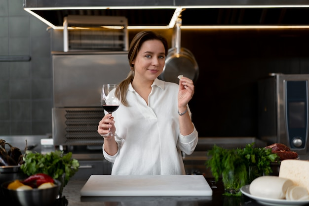 Mooie jonge kaukasische meisje permanent in keuken in een wit uniform glimlachend en rode wijn proeven leuke vrouw 30s jaar oud in wit overhemd met voedsel ingrediënten kaas vlees groenten drinken