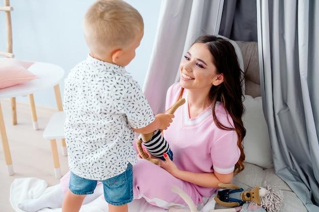 Mooie jonge kaukasische moeder zittend op de vloer in de kinderkamer spelen met gelukkig kleine kleuter zoon glimlachen