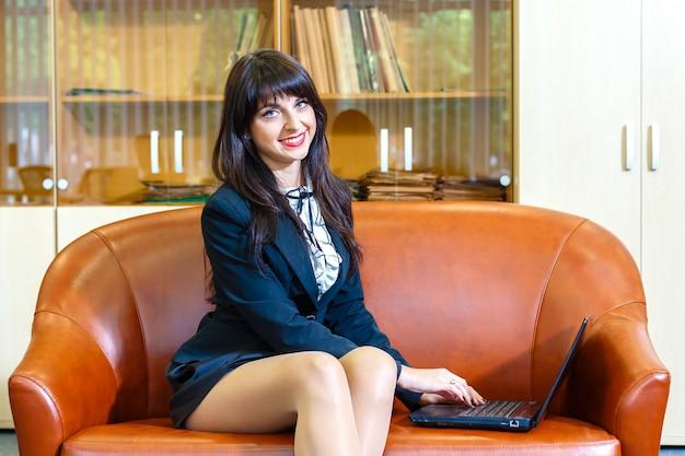 Mooie jonge kaukasische onderneemster die aan laptop werkt.