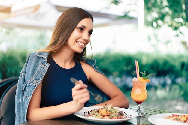 Mooie jonge kaukasische vrouw die verse caesar salade eet