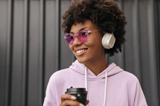 Mooie jonge krullende vrouw in roze hoodie, kleurrijke zonnebril glimlacht, luistert naar muziek in koptelefoon en houdt koffiekopje in de buurt van zwarte muur