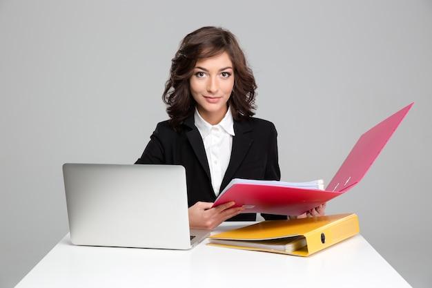 Mooie jonge krullende zelfverzekerde secretaresse die met computer en kleurrijke mappen werkt