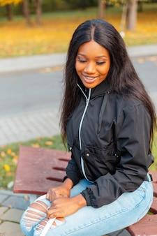 Mooie jonge lachende afro-amerikaanse meid met een zwarte jas en mallen zit op een bankje in het park