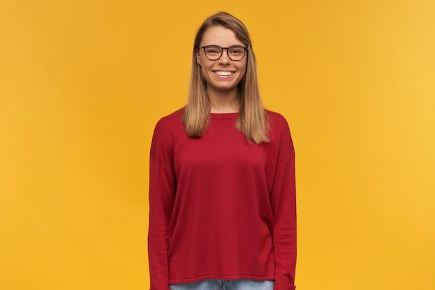Mooie jonge lachende blonde jonge meisje, op zoek blij naar de camera, rode trui en bril dragen