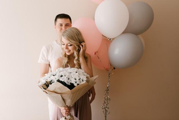 Mooie jonge lachende blonde vrouw en man met ballonnen en bloemen van margrieten of chrysanten op een lichte muur