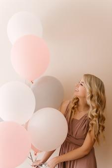 Mooie jonge lachende blonde vrouw met witte grijze en roze ballonnen op een lichte muur