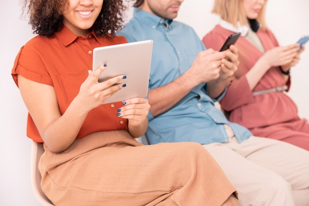 Mooie jonge lachende mixed-race vrouw in vrijetijdskleding kijken naar online video in touchpad zittend op de achtergrond van haar vrienden