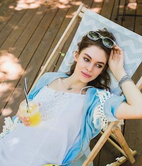 Mooie jonge lachende stijlvolle vrouw zittend in een ligstoel in zomer outfit, het dragen van witte jurk, blauwe cape, zonnebril, tas, vers sap drinken, ontspannen
