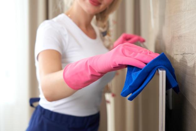 Mooie jonge lachende vrouw huis schoonmaken met microfiber doek. vrouw tv schoonmaken met reinigingsmiddel thuis, close-up. jonge vrouw gelukkig reinigen van het meubilair van de woonkamer thuis