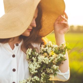Mooie jonge lachende vrouw in vintage jurk en strooien hoed in wilde bloemen veld. het meisje houdt een mand met bloemen vast