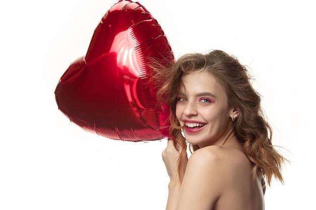 Mooie jonge lachende vrouw met lang golvend zijdeachtig haar, natuurlijke make-up met hand in de buurt van kin geïsoleerd op wit