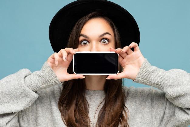 Mooie jonge lachende vrouw met mooie ogen met zwarte hoed en grijze trui met telefoon