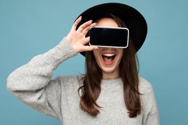 Mooie jonge lachende vrouw met zwarte hoed en grijze trui met telefoon holding