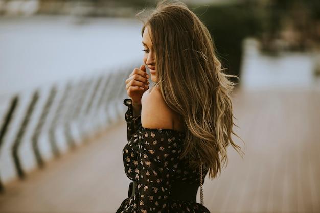 Mooie jonge langharige brunette vrouw die op de rivier loopt