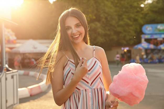 Mooie jonge langharige vrouw in lichte zomerjurk met riemen die vrolijk kijken, haar haren aanraken en oprecht glimlachen, staande boven pretpark op zonnige dag