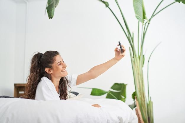 Mooie jonge latina-vrouw neemt een selfie liggend op het bed influencer deelt op sociale media