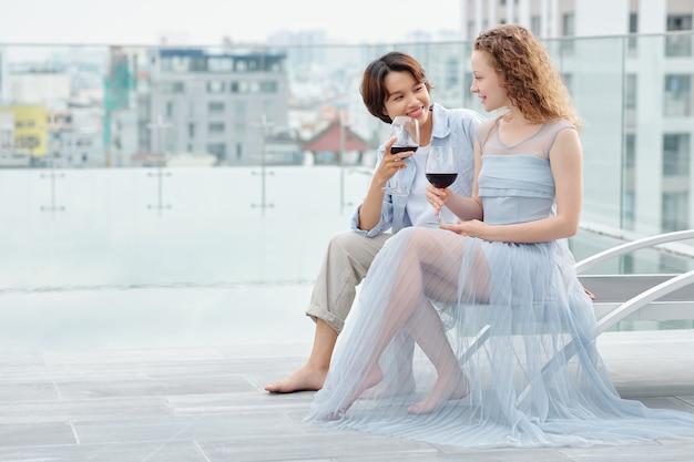 Mooie jonge lesbische vrouwen die op het dak zitten, praten en lekkere rode wijn drinken