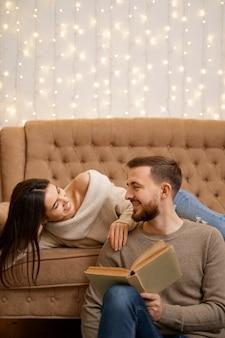 Mooie jonge liefdevolle paar binding aan elkaar en glimlachen terwijl vrouw met een boek.