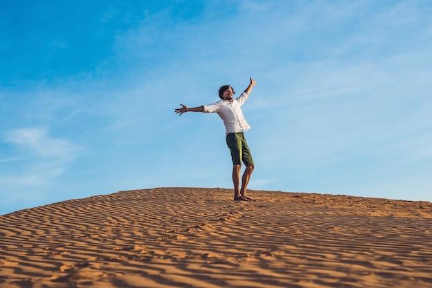 Mooie jonge man blootsvoets springen op zand in de woestijn genieten van de natuur en de zon. plezier, vreugde en
