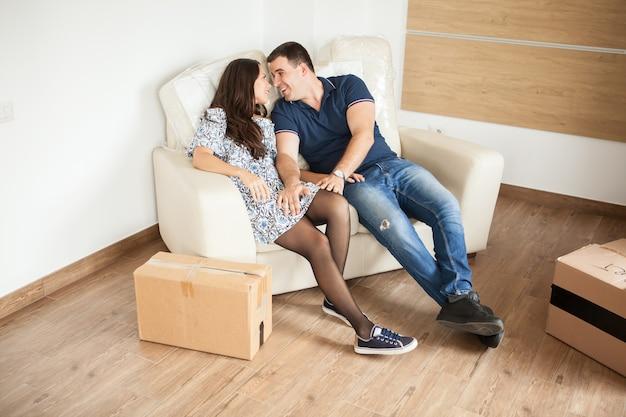 Mooie jonge man en vrouw genieten van hun nieuwe bank in hun nieuwe huis. paar op zoek naar elkaar en hebben een geweldige tijd.