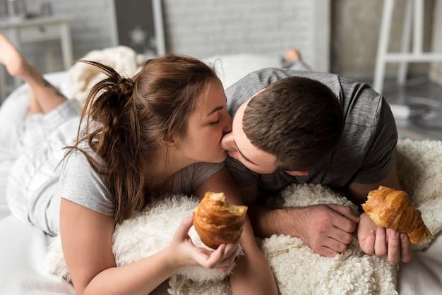 Mooie jonge man en vrouw kussen in bed