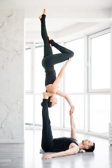 Mooie jonge man en vrouw praktijk paar acro yoga oefening in witte fitnessstudio samen met grote ramen
