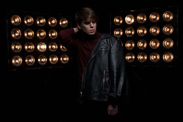 Mooie jonge man in een zwarte modieuze leren jas in rode golf en zwarte spijkerbroek staat en poseren in een donkere kamer in de buurt van heldere vintage professionele lampen. stijlvol guy star-model. mode