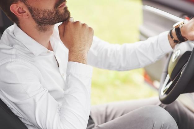 Mooie jonge man in volledig pak tijdens het autorijden.