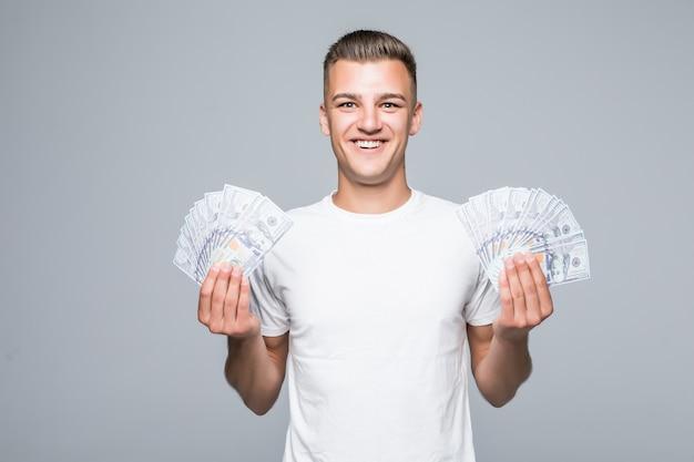 Mooie jonge man in wit t-shirt houdt veel dollarbiljetten in zijn handen geïsoleerd op een witte achtergrond