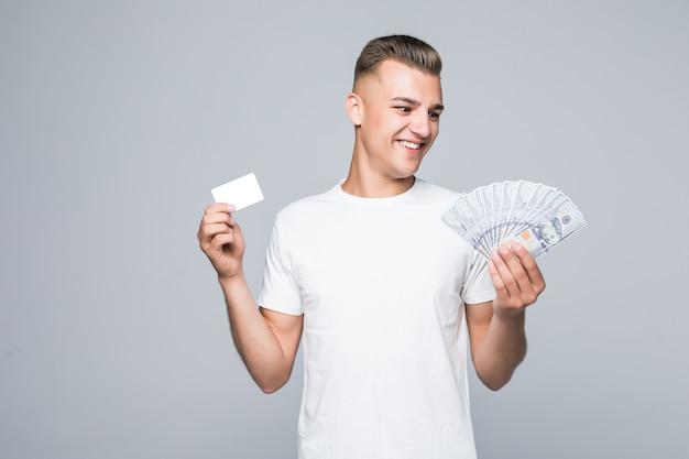 Mooie jonge man in wit t-shirt houdt veel dollarbiljetten in zijn handen geïsoleerd op wit