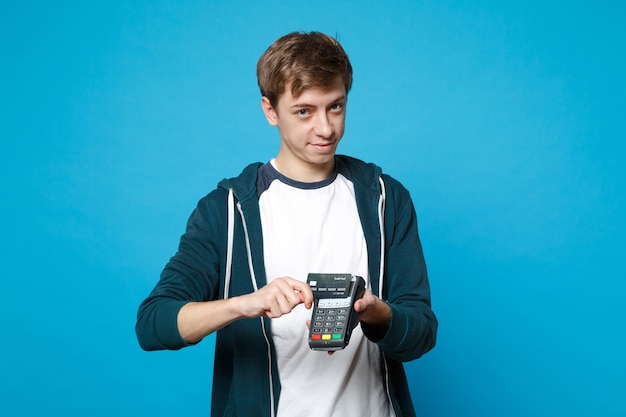 Mooie jonge man met draadloze moderne bankbetaalterminal om creditcardbetalingen geïsoleerd op blauwe muur te verwerken en te verwerven. mensen oprechte emoties, lifestyle concept.