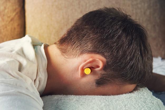 Mooie jonge man slapen, in de oren gele oordopjes tegen straatlawaai, redding van luidruchtige buren. wanneer slaap voorkomen.