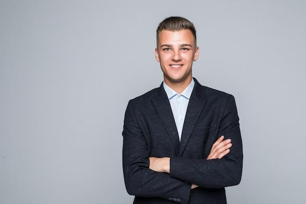 Mooie jonge man student zakenman in jas houdt zijn armen gekruist geïsoleerd op lichtgrijze muur