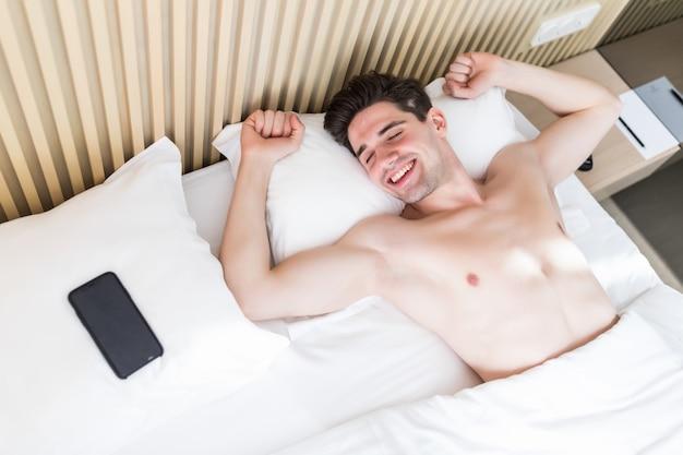 Mooie jonge man wakker op bed in de ochtend met telefoon op kussen