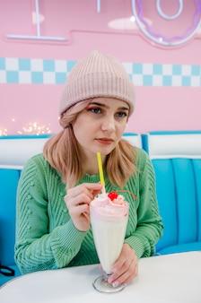 Mooie jonge meisje het drinken vanillemilkshake in koffie