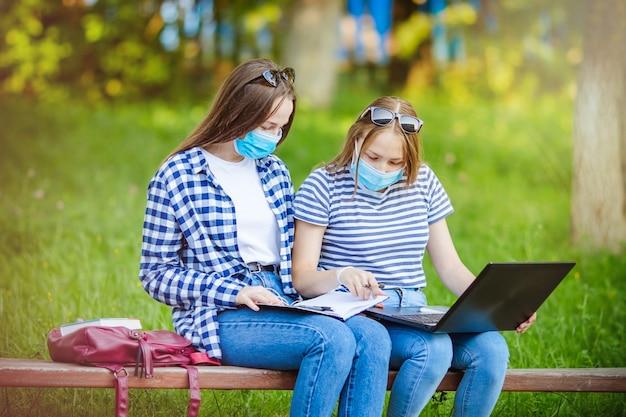 Mooie jonge meisjes die een coronavirusmasker dragen, studenten die op een parkbank in de zomerpaal zitten met een laptop en aktetas, het concept van leren op afstand of werken tijdens een pandemie, covid-19.