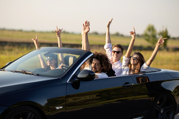 Mooie jonge meisjes en jongens in zonnebrillen glimlachen en rijden in een zwarte cabriolet op de weg met hun handen omhoog op een zonnige dag. .