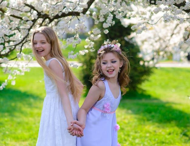 Mooie jonge meisjes met blauwe ogen in een witte jurk in de tuin met bloeiende appelbomen plezier maken en genieten van de geur van bloeiende lentetuin